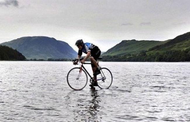 Deportista realiza truco de cruzar lago en su bicicleta