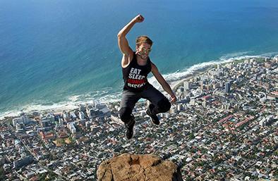 Joven salta sobre el borde de una montaña