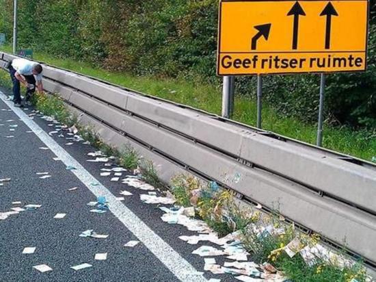 Cientos de billetes salen volando  en una  carretera
