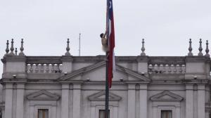 Un hombre desnudo trepa a un mástil frente al palacio de Gobierno de Chile