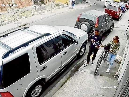 Una pareja en bicicleta roba accesorios de carros