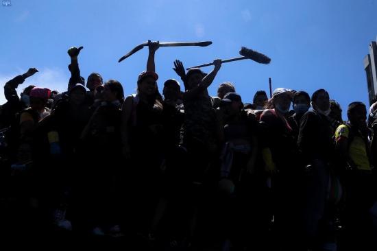 Los ecuatorianos borran huellas de las protestas armados con escobas y palas