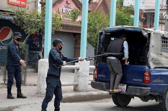 La Policía nepalí usa un gancho extensible para detener a quienes se saltan la cuarentena